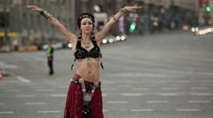 Young girl in etnic costume dancing tribal on the city. In the background a city Stock Footage