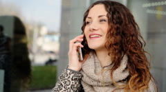 Young lady having conversation with her friends on the mobile phone in the Stock Footage