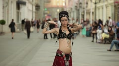 Young girl in etnic costume dancing tribal on a busy street with many people Stock Footage