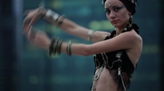 Young girl in etnic costume dancing tribal on the background of city skyscrapers Stock Footage