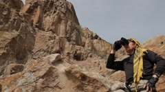 A man dressed in Bedouin scarf looking through binoculars among the rocks Stock Footage