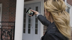 Side portrait of a beautiful blond girl using a smart phone to network, taking - stock footage