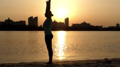 Girl Doing the Pose Downward-Facing Dog. the Action at Sunset Near River. Stock Footage