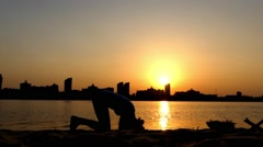Girl Does a Headstand at Sunset Near the River. Stock Footage