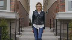 Beautiful young woman walking on the street. Blonde confident gait moves the Stock Footage