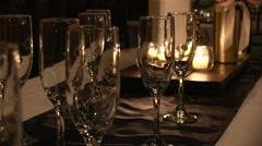 Zoom out of champagne glasses and lit candles candle at wedding reception Stock Footage