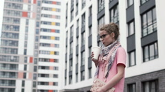 Young woman drinking coffee in the city.  smiling and looking at the camera Stock Footage