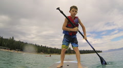 Boy on paddle board on lake - stock footage