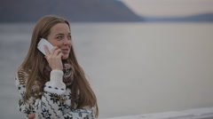 The young female is watching into the distance talking on the mobile phone being Stock Footage