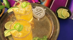 Spicy grapefruit margarita cocktail garnished with lime and jalapenos. - stock footage