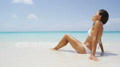 Beach bikini woman sun tanning on summer vacation travel holidays in paradise - stock footage