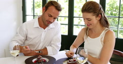 Cute couple making each other taste their deserts - stock footage