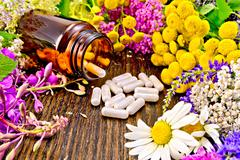 Capsules in brown jar with flowers on board - stock photo