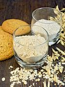 Flour and bran oat in glass with cookies on board - stock photo