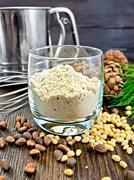 Flour cedar in glass with sieve on board - stock photo