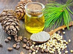 Flour cedar in spoon with oil on dark board - stock photo