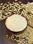 Flour oat in bowl with grain on board - stock photo