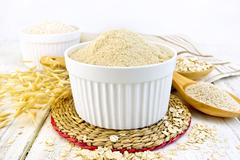 Flour oat in white bowl on board - stock photo