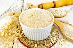 Flour oat in white bowl on light board - stock photo