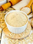 Flour oat in white bowl with bran and flakes on board - stock photo