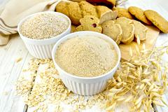 Flour oat in white bowl with bread on board Stock Photos