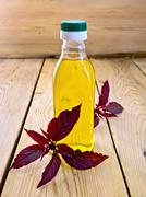 Oil with amaranth in bottle on light board Stock Photos