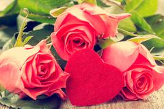 Pink roses and handmaded toy heart - stock photo