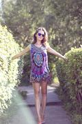 Beautiful woman standing in a bright dress among the bushes Stock Photos