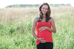 Young beautiful pregnant woman holding tummy smiling, in red a light summer Stock Photos