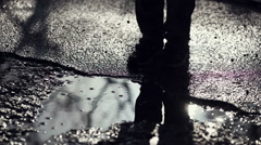 Boy jumping in puddle. Pants, socks and shoes are wet. Puddle jumping. - stock footage