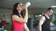 The girl in the gym drinking water from a bottle Stock Footage