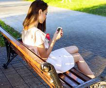 Beautiful girl sitting bench, brunette pink dress, fashion life style with your - stock photo