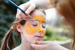 Stock Photo of Child painting process at girl's face