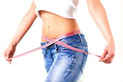 Slim Attractive Waist woman in jeans with tape measure show thin body.Diet an Stock Photos