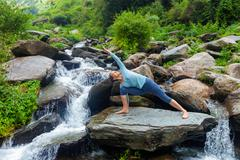Woman practices yoga asana Utthita Parsvakonasana outdoors Stock Photos