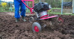Slowly pushing a cultivator to plow soil Stock Footage