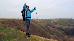 Man tourist in a blue jacket with a backpack enjoys his climbing Stock Footage