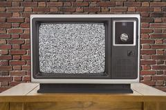 Old Television with Static Screen and Brick Wall - stock photo