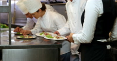 Group of chefs putting finishing touch and giving plate to the waitress Stock Footage