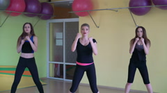 Three girls doing fitness exercises synchronously in the gym. 4K - stock footage