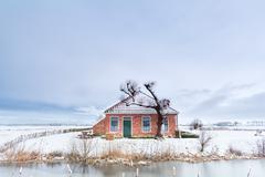 Dutch farmhouse by river in snow - stock photo
