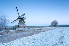 windmill by river and winter meadow in snow - stock photo