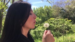 Woman blowing on Taraxacum, slow motion Stock Footage