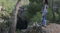 A brunette woman standing on the precipice of the canyon posing and smiling - stock footage