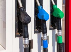 Gas pump nozzles with different fuels at the gas station - stock photo