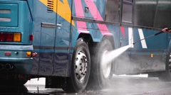 Man washes with a facility pressure wheels and bodywork of a bus Stock Footage