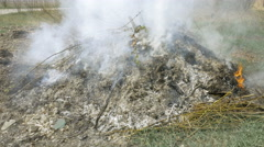 Burning grass foliage heap with heavy dense smoke Stock Footage