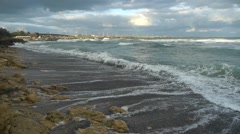 Sea waves that break the rocky shore, leading them to a beach sand near the port Stock Footage