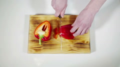 Man slicing red bell pepper on a cutting board - stock footage