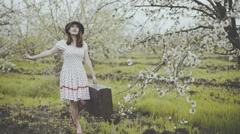 Young woman dressed in retro style posing in blooming garden slow motion Stock Footage